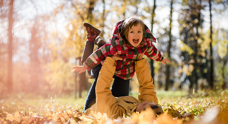 Little daughter enjoys time together with her mother in autumn nature