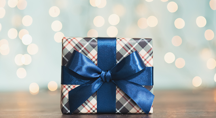 Christmas gift box against turquoise bokeh background. Holiday greeting card