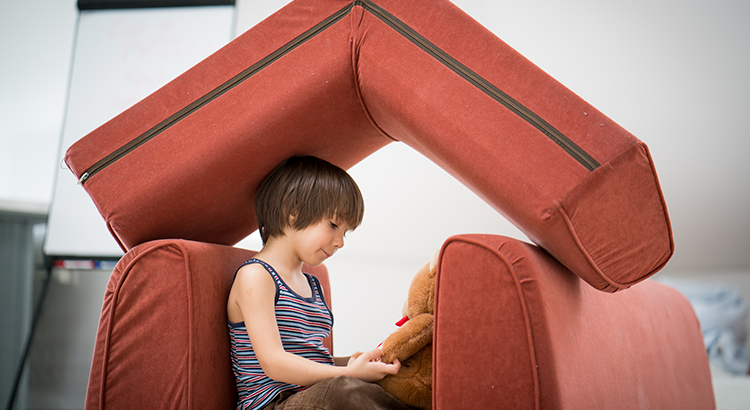 Little boy at home with Teddy bear playing with small house and roof on top made of living room furniture