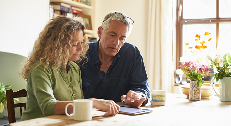 Couple sitting at table using digital tablet