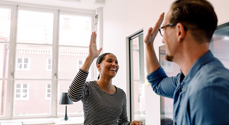 Happy businesswoman giving high-five to male colleague in office