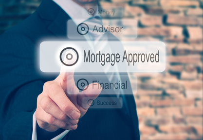 Businessman pressing a Mortgage Loan Approval concept button.