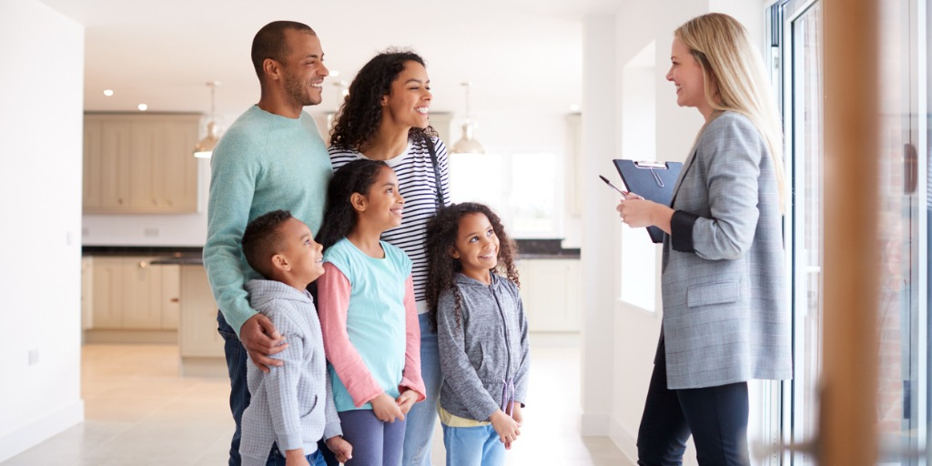 female-realtor-showing-family-interested-in-buying-around-house-picture-id1166185181 (1)